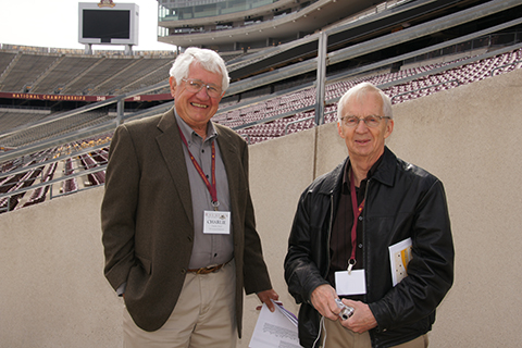 two alumni posing together in TCF bank stadium