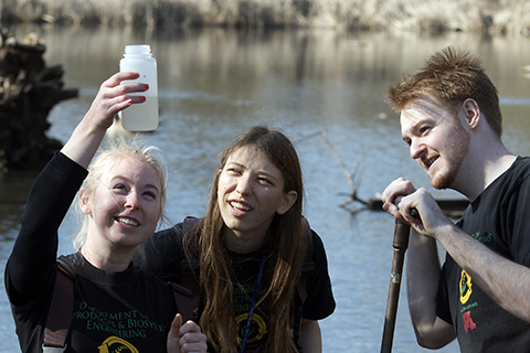 students in the field by a lake looking at a water sample