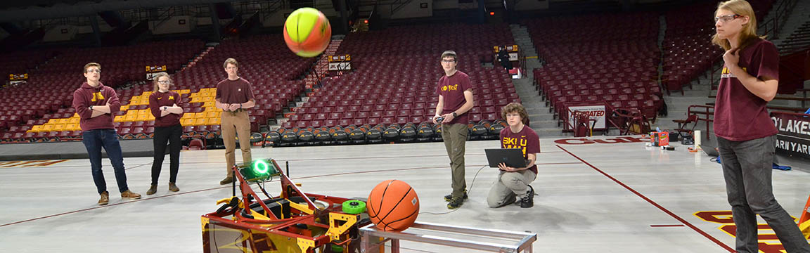 Students with basketball-shooting robot