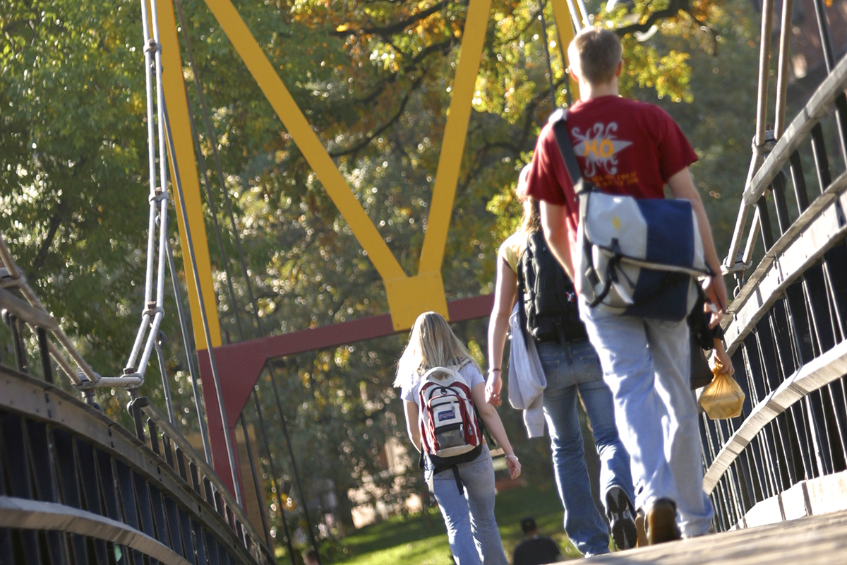 students walking across big M bridge on campus