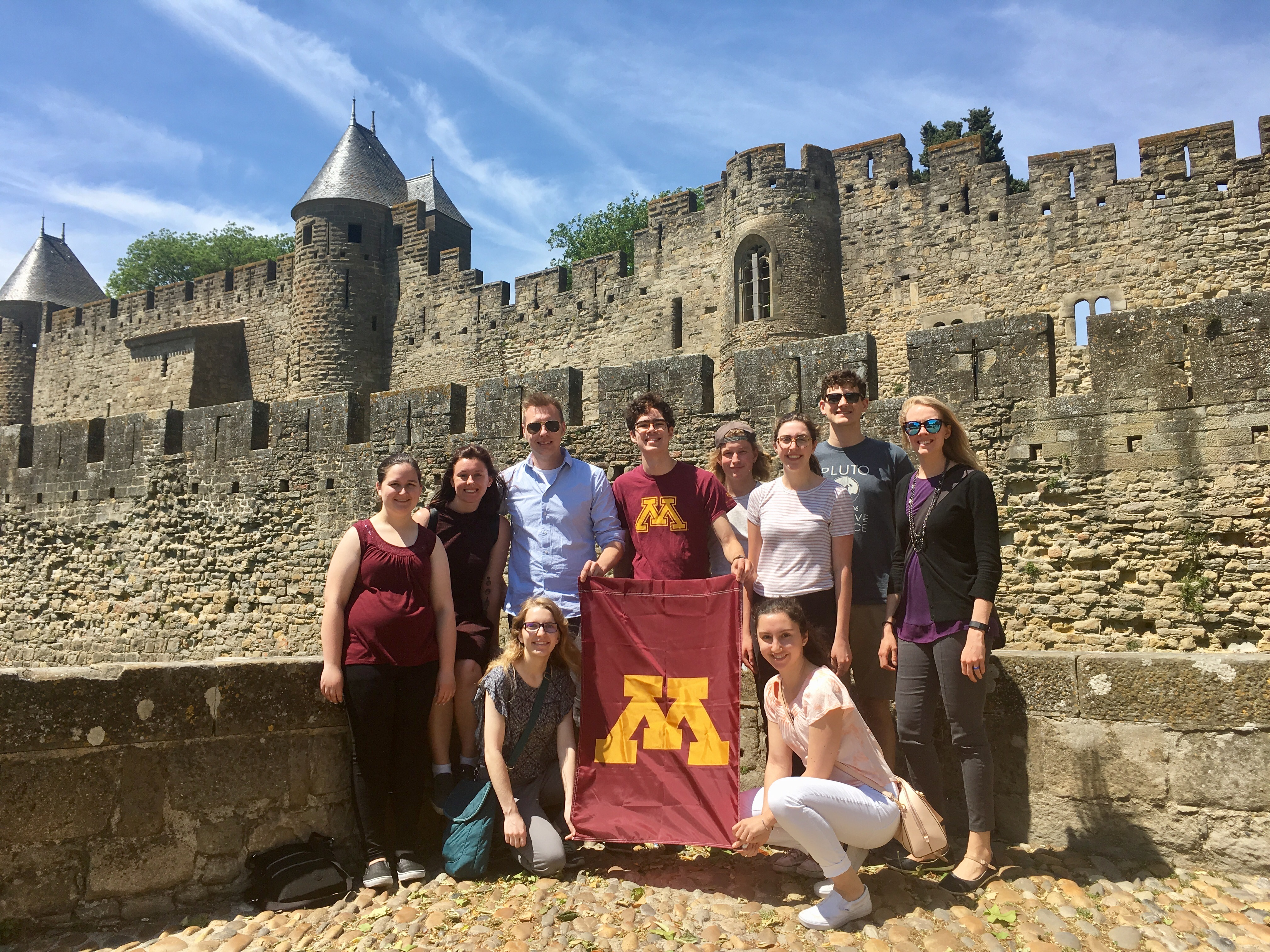 Students with U of M flag in front of castle ruins in Carcassonne, France