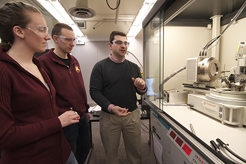students and faculty in chemical engineering lab looking at machine