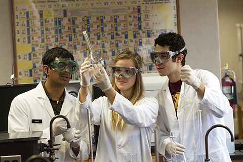 Three students in chemistry lab wearing white coats and googles looking at beaker