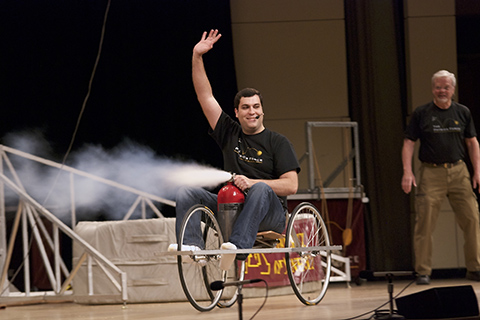 presenter on stage in cart using air to push backwards