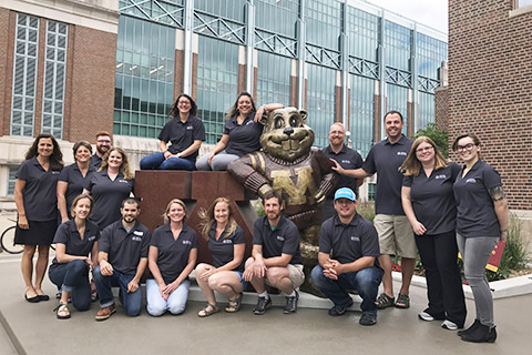group photo of trainers posing with goldy gopher statue