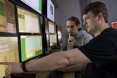 two students looking array of computer monitors