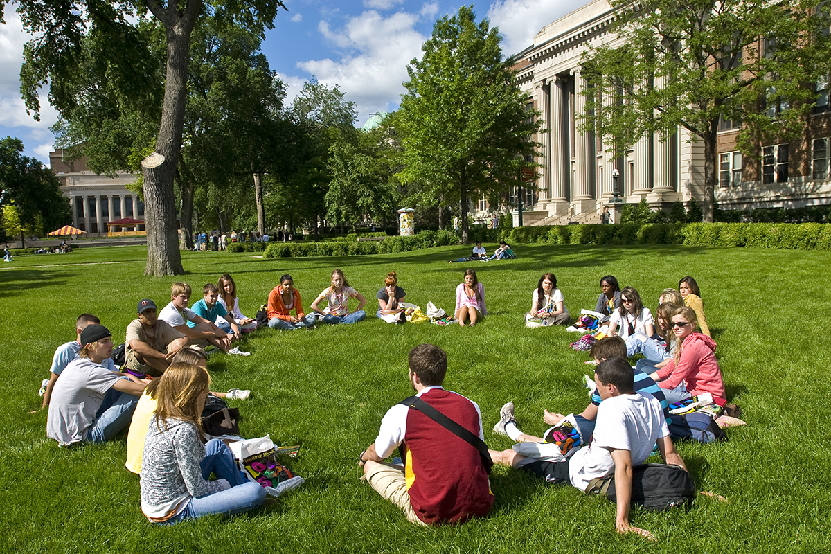 Students sitting in circle outside in a circle during orientation
