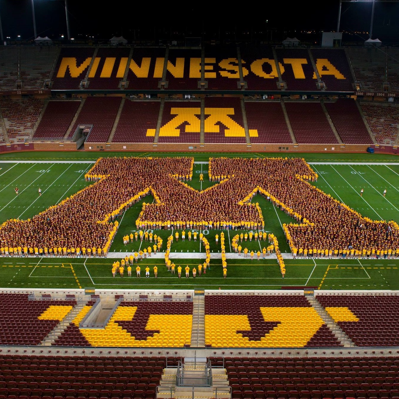 "People forming on the football field in the shape of a UMN ""M"" and ""2019"""