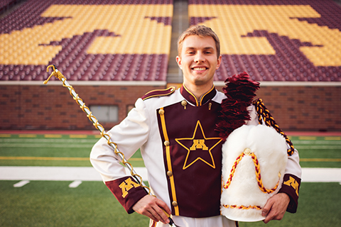 Rudin on football field smiling with drum major apparel