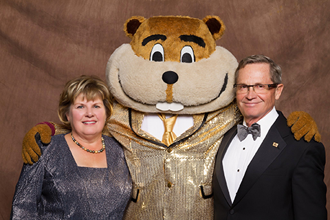 Ron and Janet Christenson posing with Goldy Gopher in a golden suit