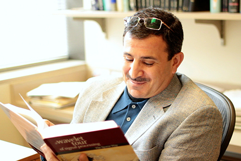 Emad Ebbini sitting in chair reading a book
