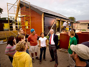 University of Minnesota President Robert Bruininks visits with students at the solar house they are building