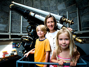 Kristen McQuinn and kids posing by telescope