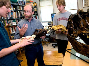 Kent Kirkby holding skulls while talking to students