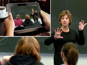 Professor teaching while student watches her on handheld device