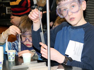 two children with goggles on conducting an activity