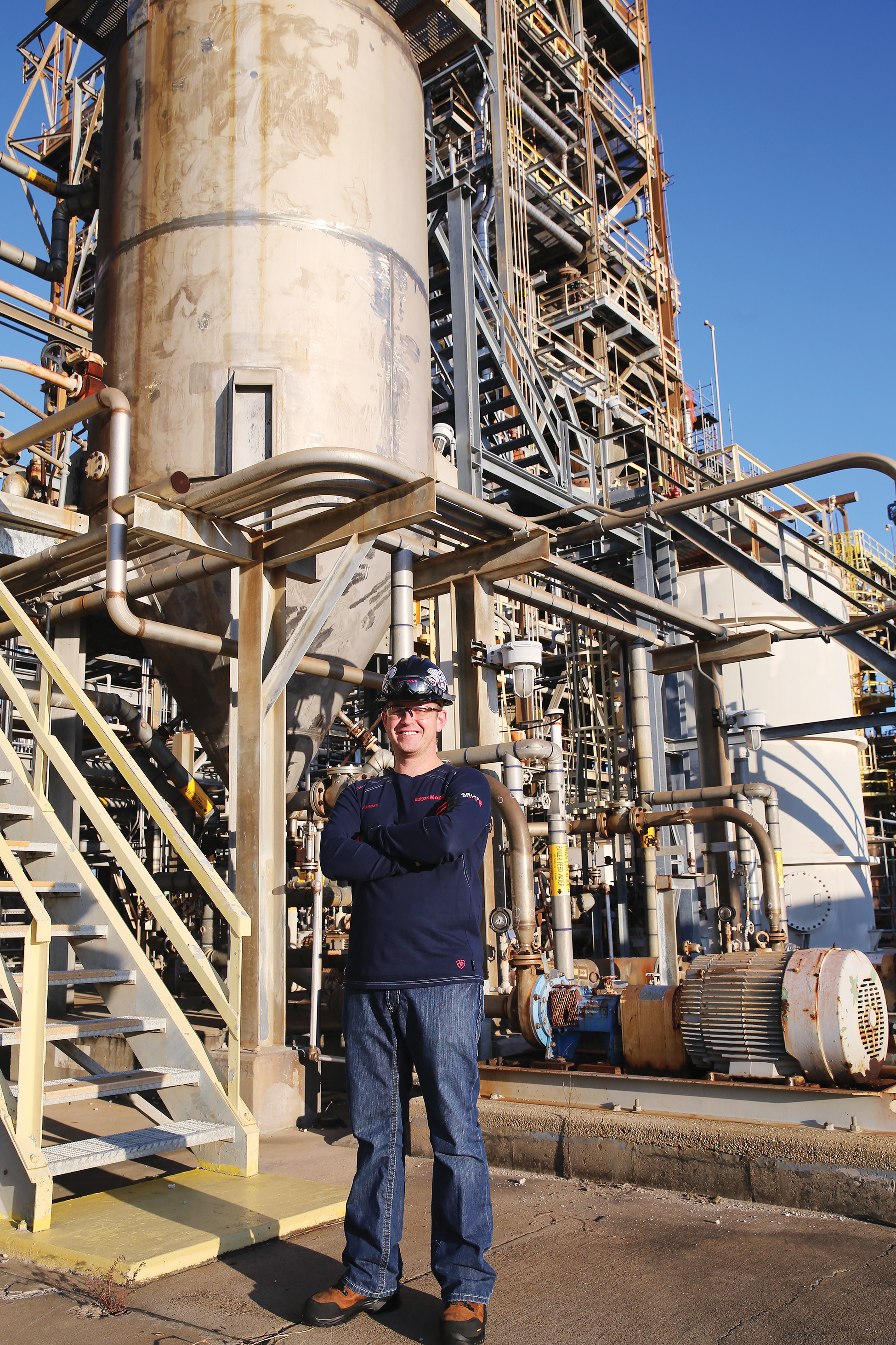 A man standing in an oil refinery.
