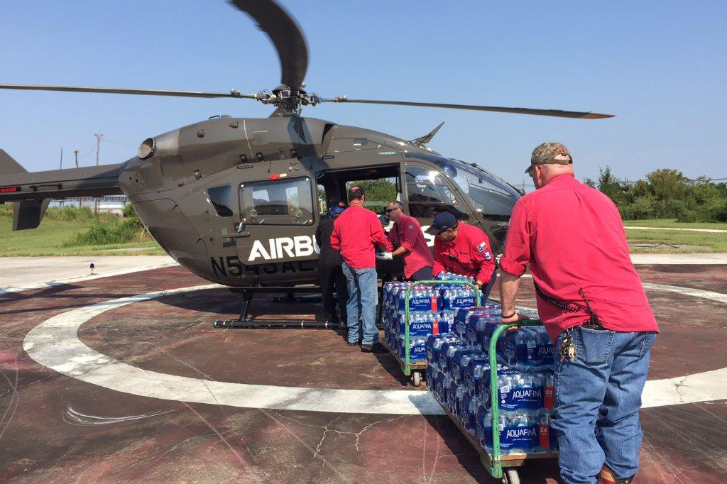 Four men loading supplies into a helicopter.