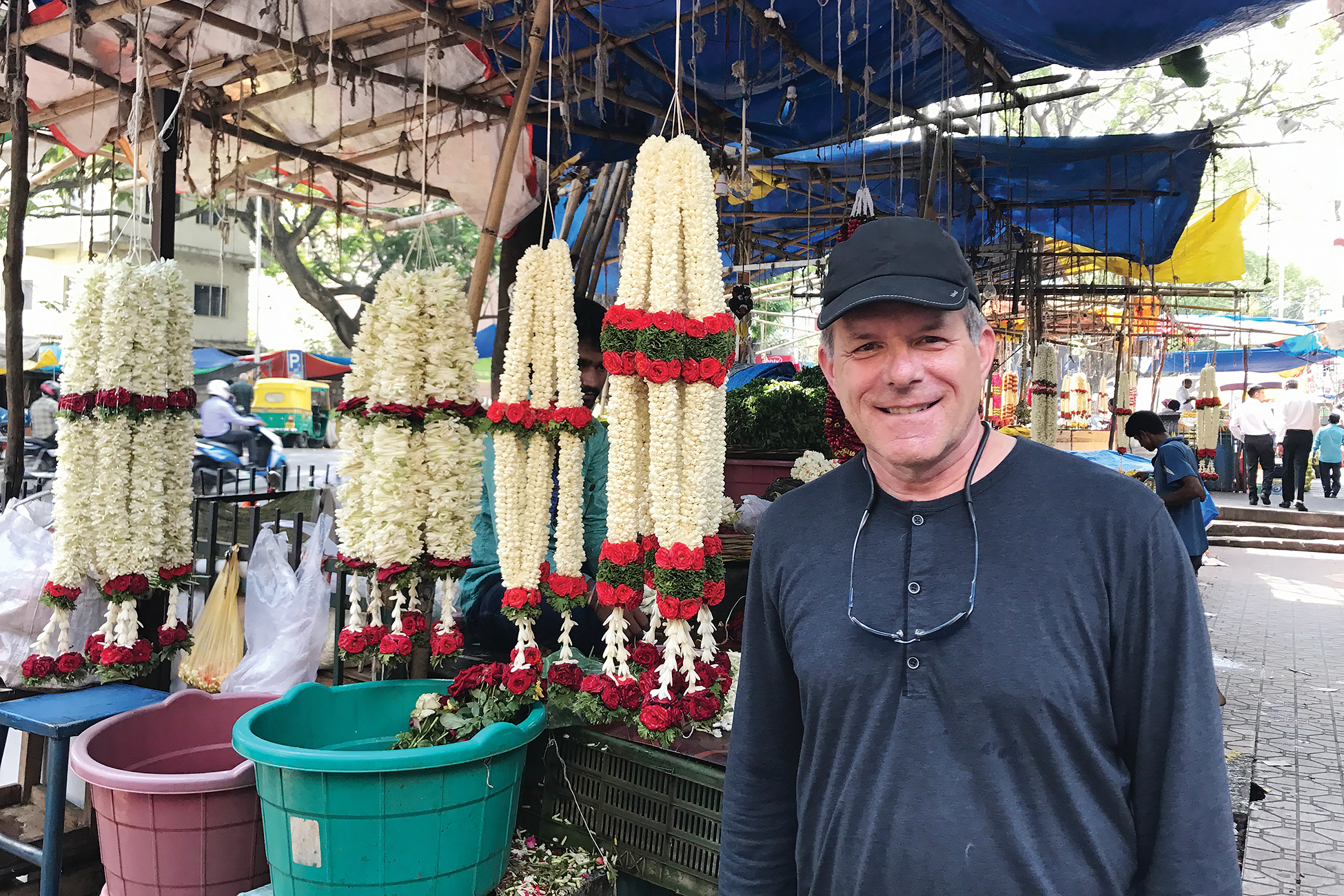 A man standing next to jasmine flower garlands.