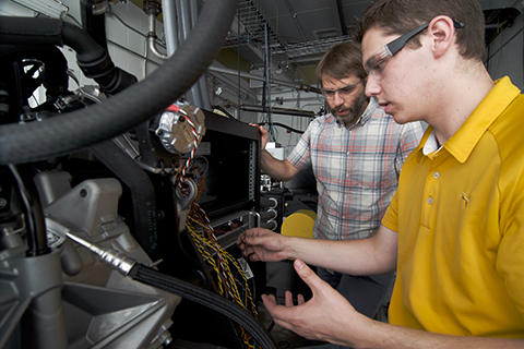 Professor and student working on an engine