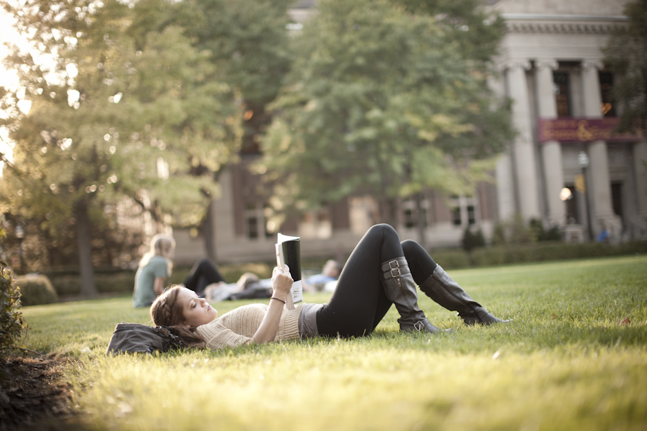 student reading outside on campus mall