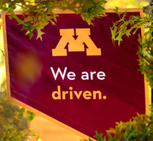 "Banner that says ""We are Driven"" with the University of Minnesota ""M"" logo"