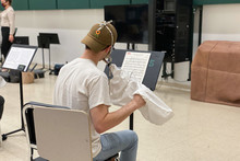 A music student plays the flute using an instrument mask.