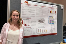A female student standing in front of a research poster.