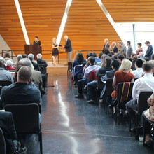 Photo of BME's undergraduate commencement reception; shows a student on stage with a faculty member, in front of an audience