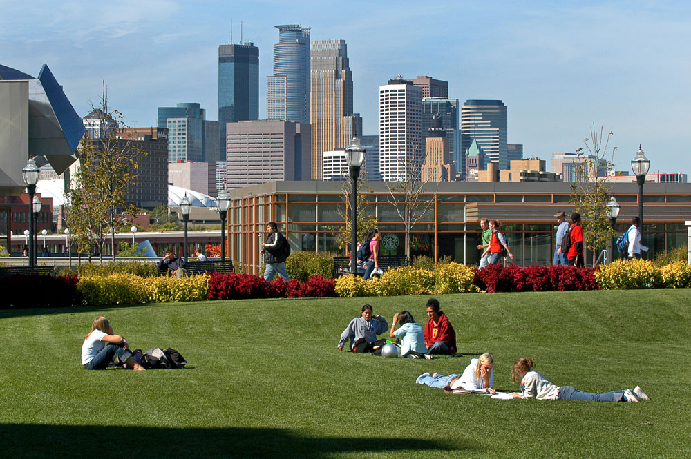 Students relaxing on the University of Minnesota campus, with the skyline in the background.